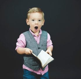Boy Shocked holding a book