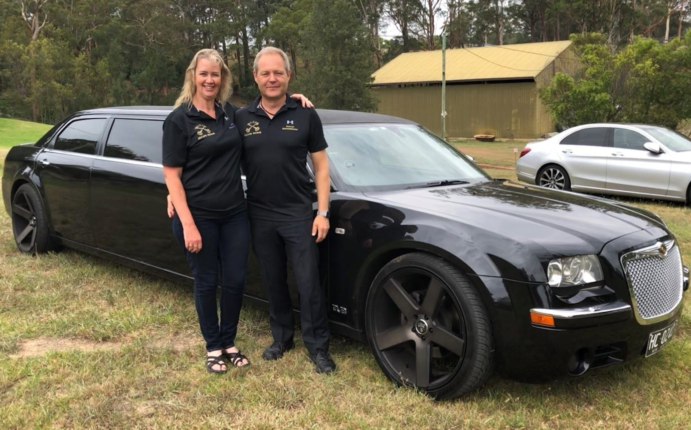 A photo of Darren and Julia, the owners of Elude, and escape room enthusiasts, both happy while standing in front of a stretched black Chrysler 300