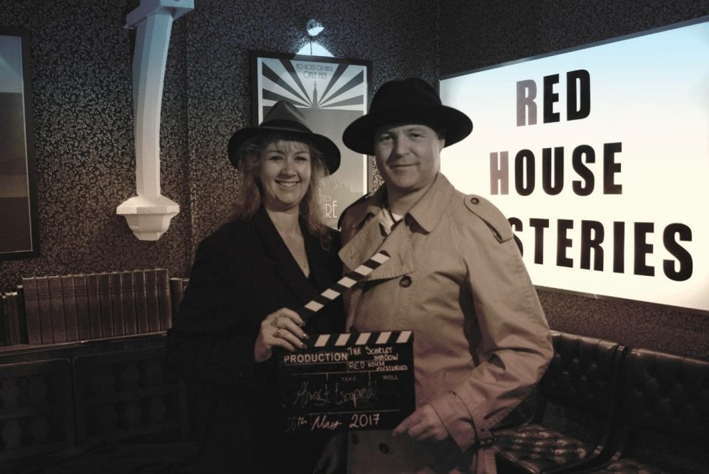 A photo of Julia and Darren with a clapperboard and in spy outfits